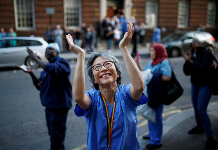 An NHS worker applauds at St Mary's hospital during the Clap for our Carers campaign in support of the NHS.