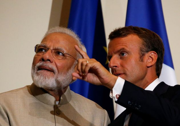 French President Emmanuel Macron gestures next to Indian Prime Minister Narendra Modi after a joint statement...