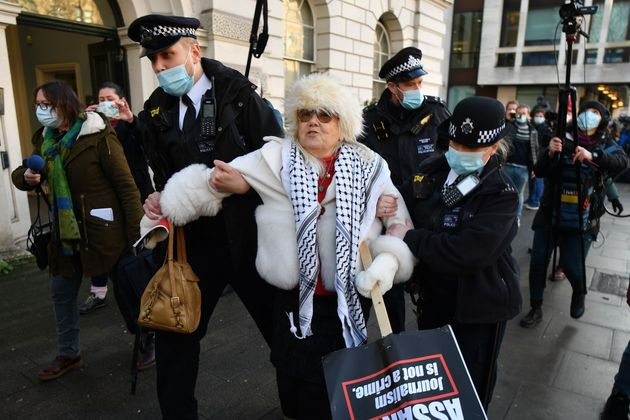 Police arrest a supporter of Wikileaks founder Julian Assange outside Westminster Magistrates court in...
