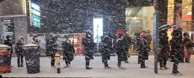 북극발 찬공기 영향으로 중부지역과 내륙을 중심으로 한파가 이어지고 있는 6일 저녁 서울 강남역 인근에서 시민들이 눈발을 맞으며 버스를 기다리고