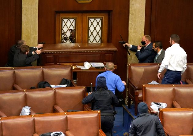 US Capitol police officers point their guns at a door that was vandalised in the House Chamber during...