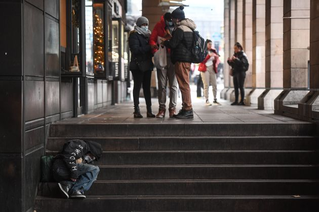 A homeless man sleeps on a set of stairs in