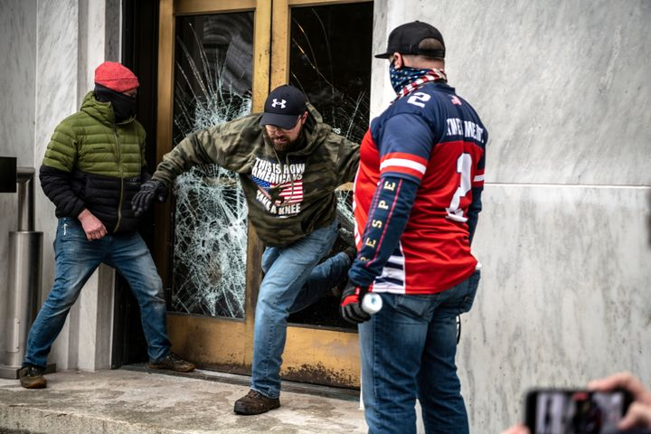 Far-right protesters break the door to the Capitol building during a protest against restrictions to prevent the spread of co
