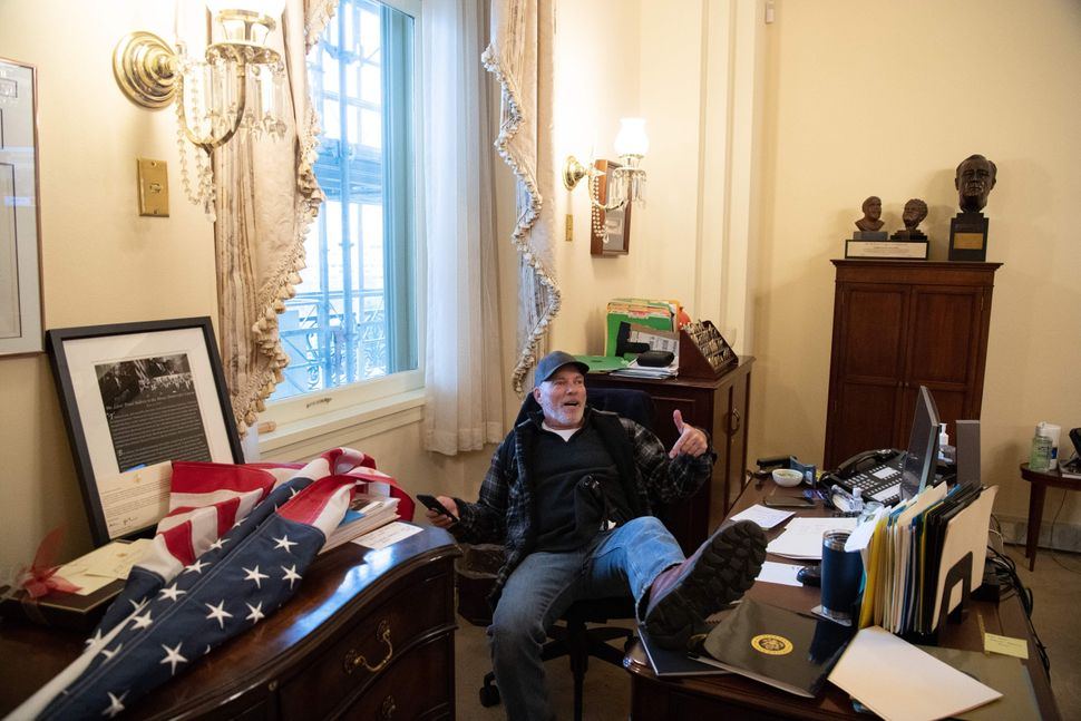 A pro-Trump rioter puts his feet up in Speaker Nancy Pelosi's offices. The desk reportedly belongs to her assistant.