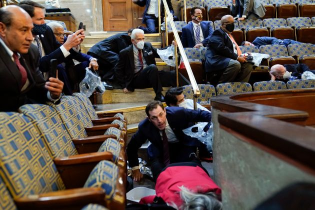 People shelter in the House gallery as protesters try to break into the House Chamber at the U.S. Capitol...