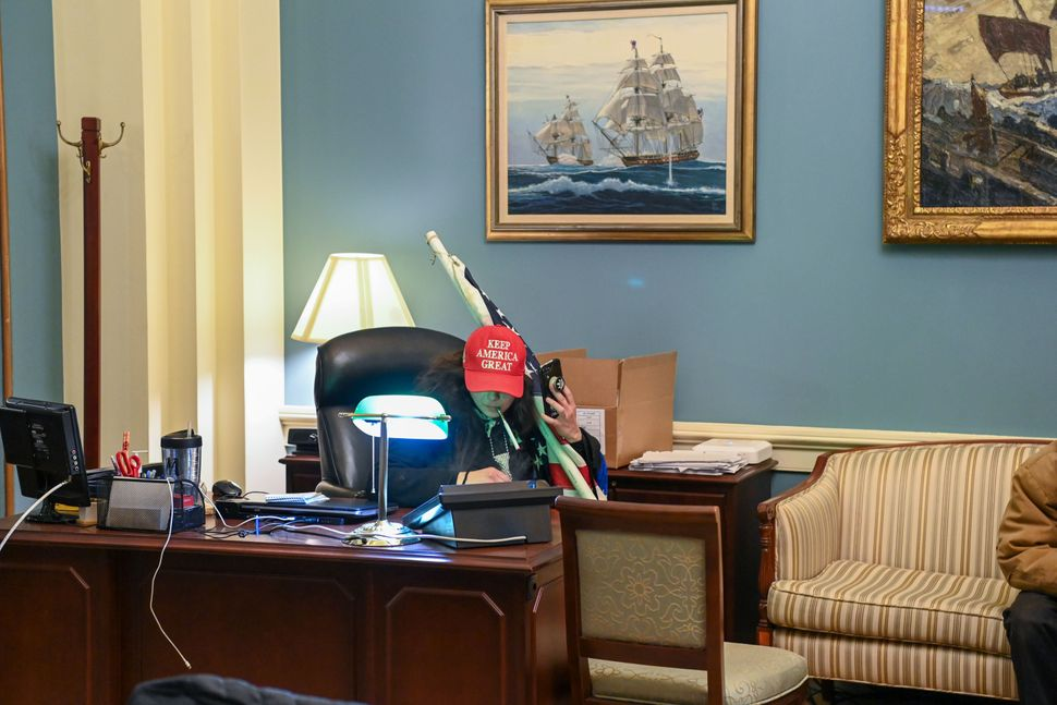 "A rioter wearing a ""Keep America Great"" hat sits in Pelosi's office suite."