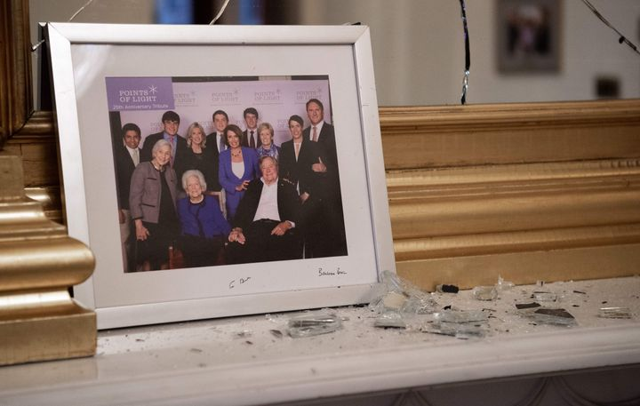 Broken glass litters a mantle in Pelosi's offices before a photo of the speaker and the late President George H.W. Bush.