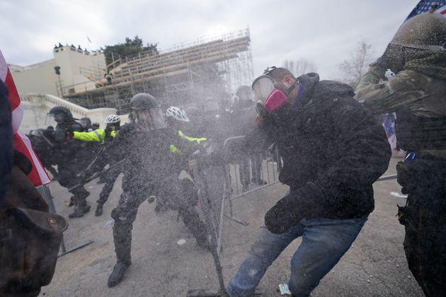 警察のバリケードを超え、議会に侵入しようとするトランプ支持者