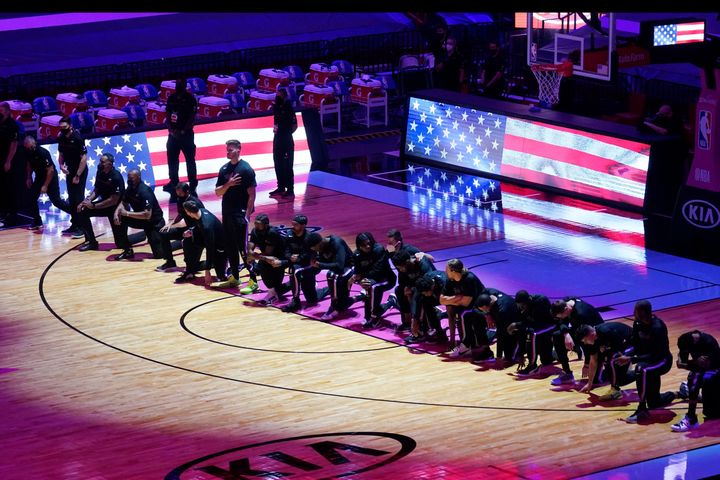 The Boston Celtics team kneels during the playing of the National Anthem before the first half of an NBA basketball game agai