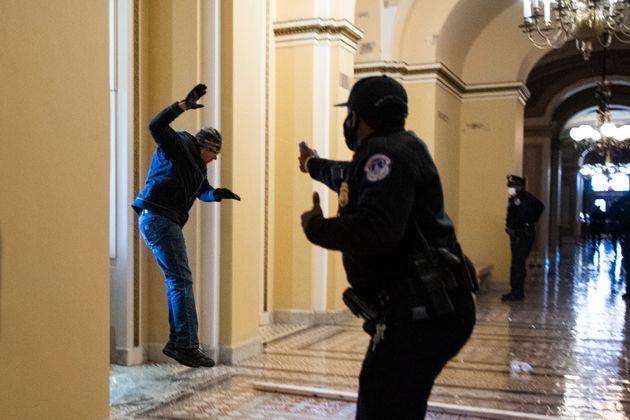 窓を割って入ってきたトランプ支持者に銃を向ける警官