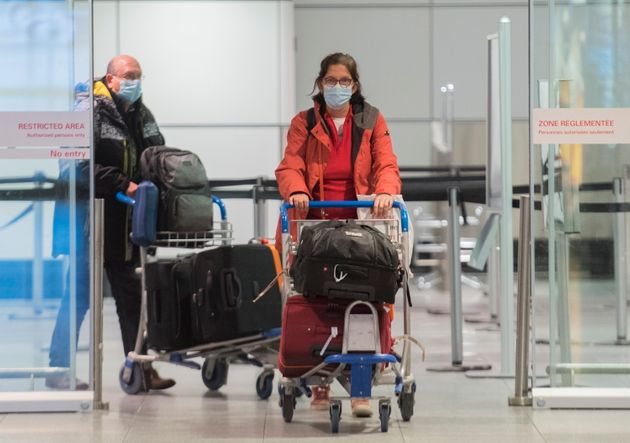 Passengers are shown in the international arrivals hall at Montreal-Trudeau Airport in