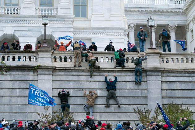 Supporters of President Donald Trump climb the west wall of the Capitol on