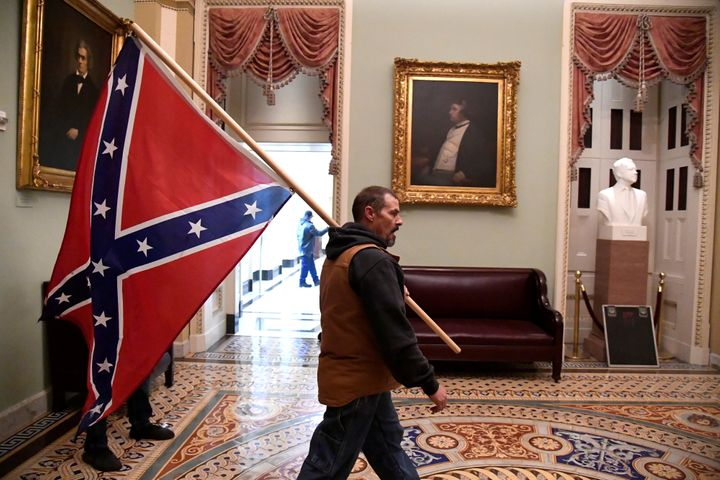 A Trump supporter carried a Confederate battle flag on the second floor of the U.S. Capitol near the entrance to the Senate a
