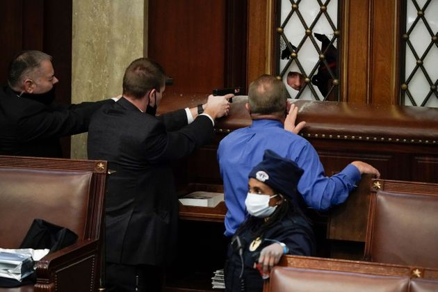 議事堂に侵入しようとするトランプ支持者に銃口を向ける警察
