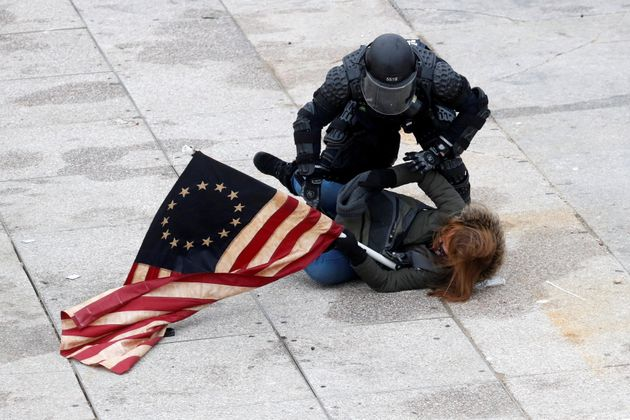 A police officer detains a pro-Trump protester as mobs storm the U.S. Capitol, during a rally to contest...