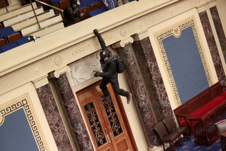 A pro-Trump rioter hangs from the balcony in the Senate Chamber.