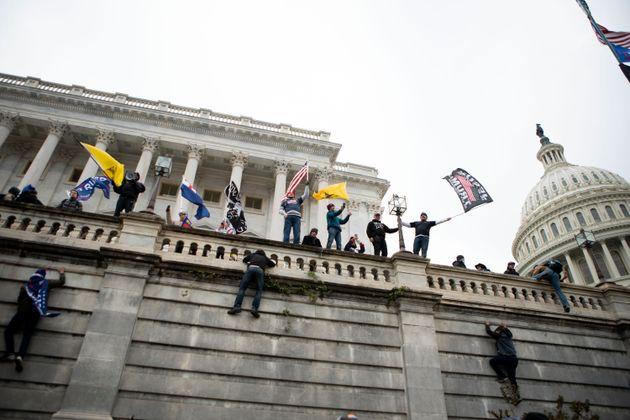 連邦議事堂の壁によじ登って旗を降る支持者らも