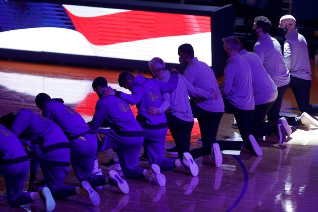 Les joueurs des Golden State Warriors, genou à terre lors de l'hymne américain avant le...