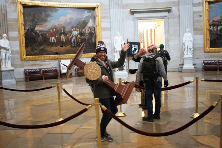 A pro-Trump rioter carries the lectern of U.S. Speaker of the House Nancy Pelosi after a mob stormed the Capitol building on Jan.  6, 2021.