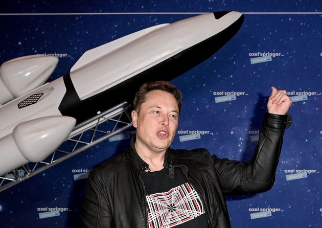 SpaceX owner and Tesla CEO Elon Musk (R) gestures as he arrives on the red carpet for the Axel Springer...