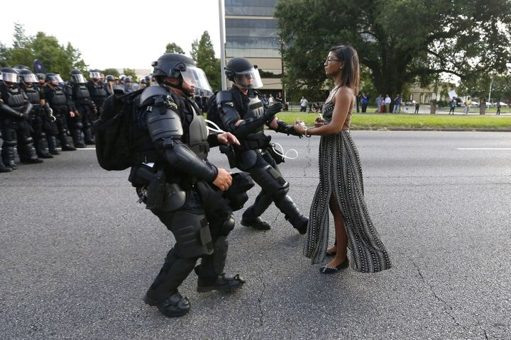 Activist Ieshia Evans stands her ground while offering her hands for arrest as she is charged by riot police during a protest