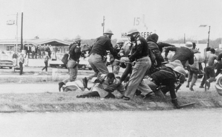 John Lewis (center, in the light coat) attempts to ward off a blow from a state trooper as civil rights activists marched fro
