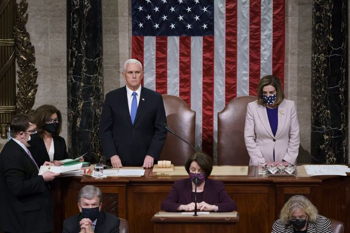 Vice President Mike Pence and Speaker of the House Nancy Pelosi read the final certification of Electoral College votes cast in November's presidential election on Thursday, January 7, 2021.