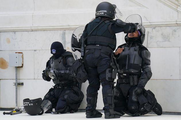 Un agente del Capitolio ayuda con unas gotas a un compañero, afectado por los gases lanzados contra...