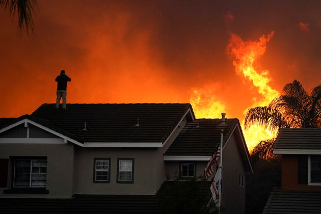 Herman Termeer, 54, stands on the roof of his home as the Blue Ridge Fire burns along the hillside in...