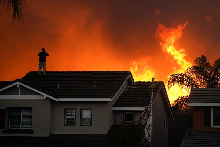 Herman Termeer, 54, stands on the roof of his home as the Blue Ridge Fire burns along the hillside in Chino Hills, Calif., on