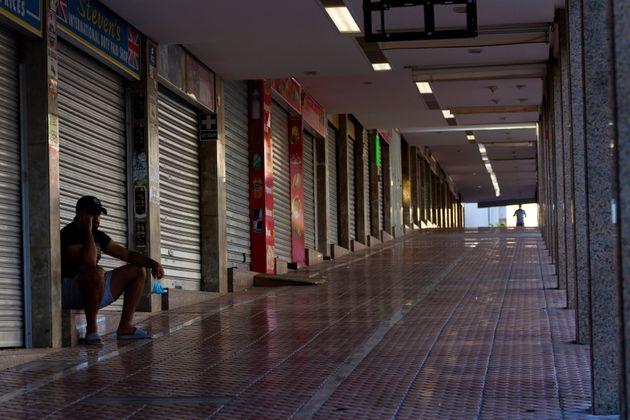 Un hombre descansa en una calle comercial de Magaluf, completamente cerrada, el pasado