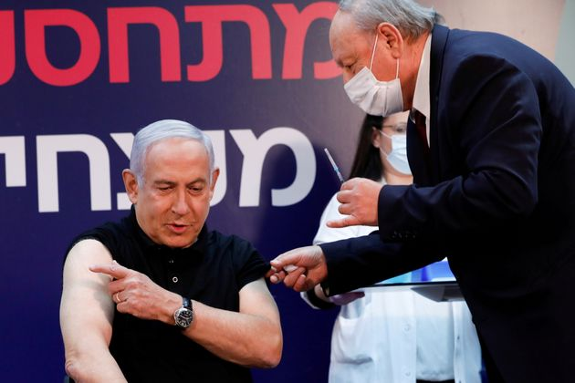 First in line: Israeli Prime Minister Benjamin Netanyahu gets ready to receive a coronavirus vaccine...