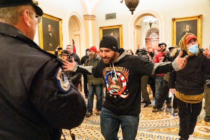 Un partisan de Donald Trump, vu portant une chemise QAnon, se confronte à des officiers de la police du Capitole devant la salle du Sénat.