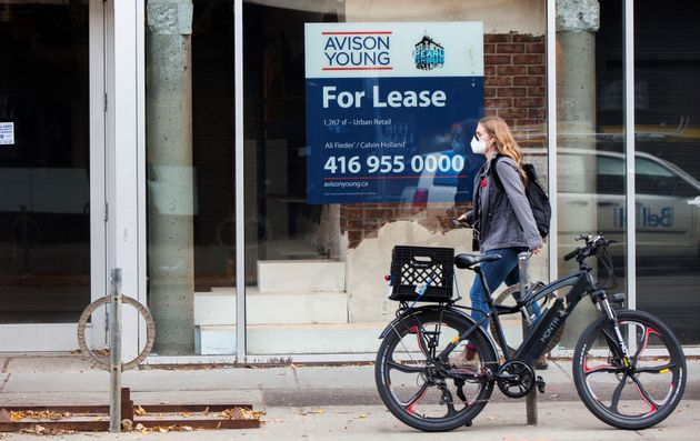 A woman wearing a face mask walks on a street in Toronto, Nov. 6, 2020. Canada's job recovery stalled...