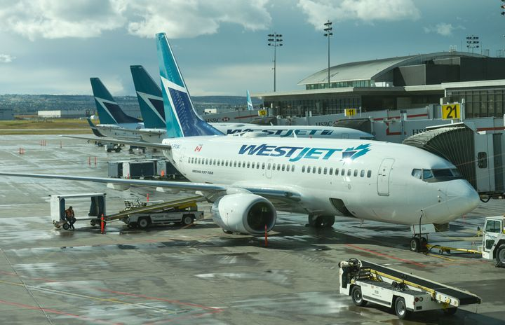 A view of WestJet planes at Calgary International Airport, Mon. Sept. 10, 2018. WestJet is laying off staff in the wake of new federal COVID-19 testing requirements for Canada-bound passengers.