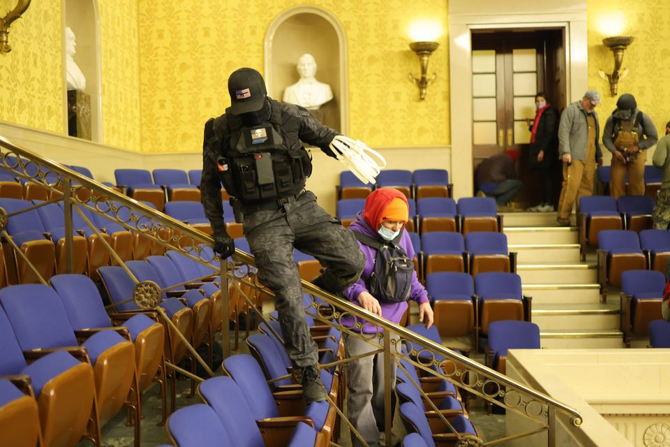 A rioter dressed in tactical gear carries zip-tie handcuffs in the Senate Chamber on