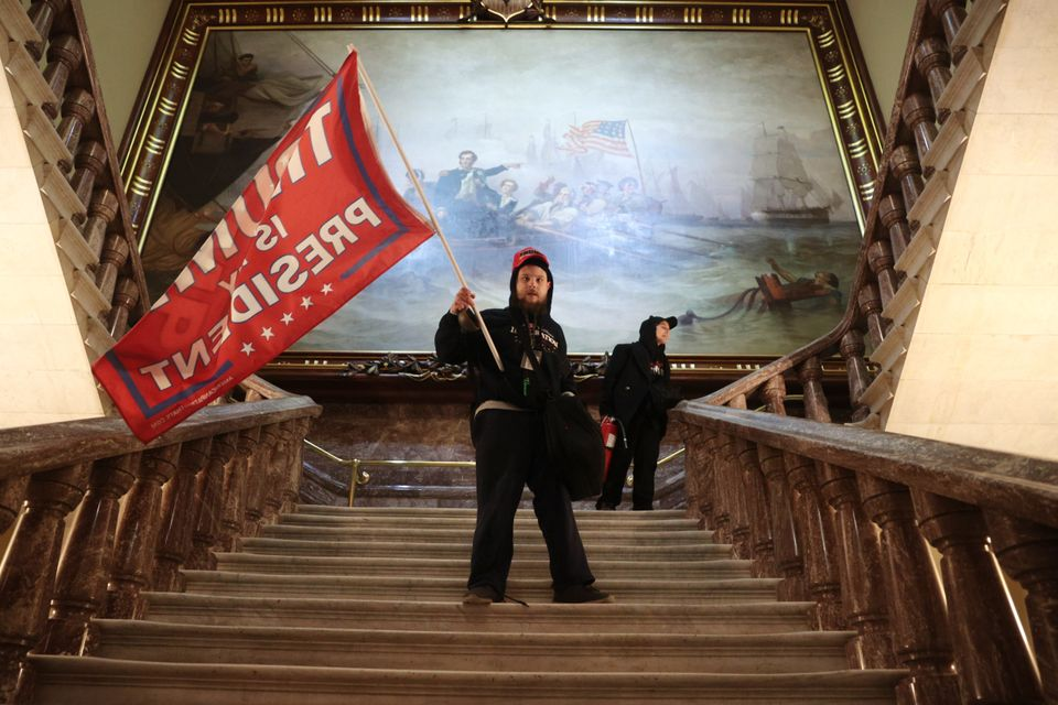 A rioter holds a Trump flag inside the Capitol near the Senate Chamber on