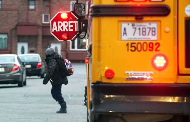 Young boy getting off a school bus in Montreal, Que., Thursday, December 3,
