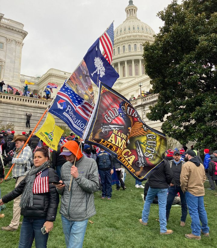 People hold flags glorifying violence and religion near the U.S. Capitol, which was breached on Jan. 6 by thousands of rioter