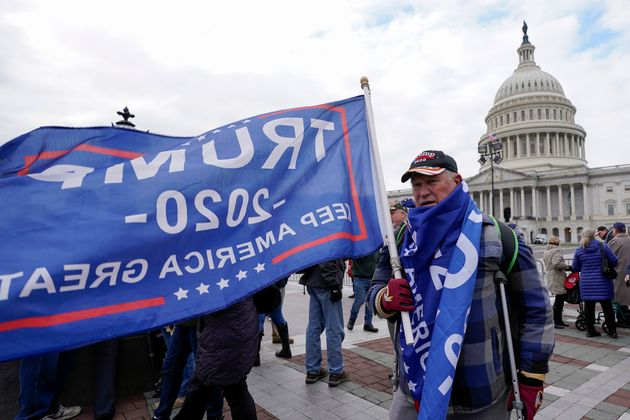 Supporters of President Donald Trump cary flags and banners on Capitol Hill during a rally, Wednesday,...