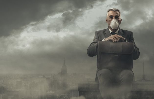 Businessman sitting on a rooftop in a polluted city, he is pensive and looking away: business and pollution