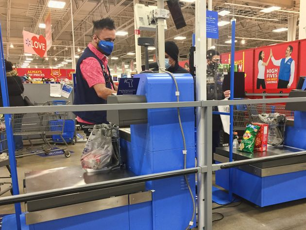 Man wearing a face mask while doing self-checkout at a Walmart store during the novel coronavirus (COVID-19)...