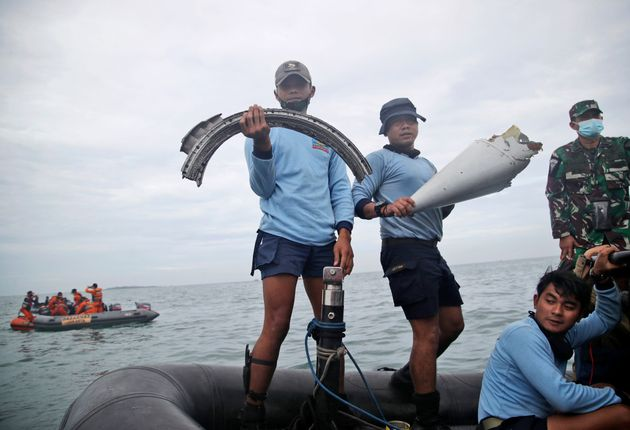Indonesian Navy divers show parts of an aircraft recovered from the water during a search operation for...
