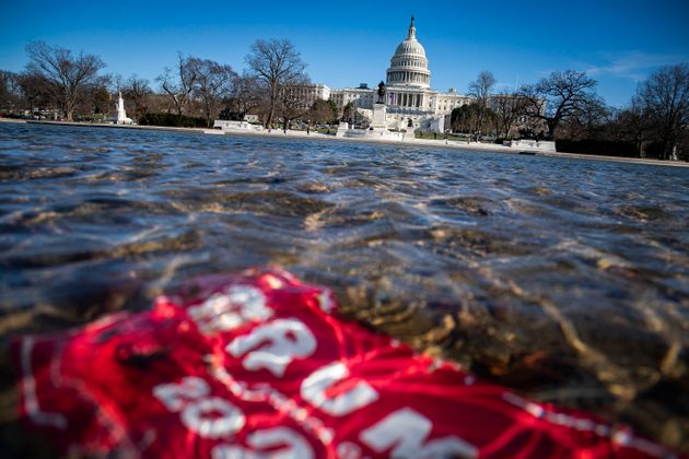 WASHINGTON, DC - JANUARY 09: A campaign sign for U.S. President Donald Trump lies beneath water in the...