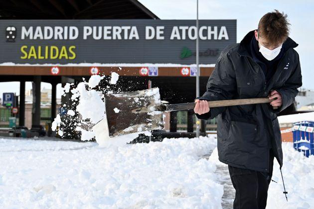 Un hombre ayuda a quitar nieve cerca de la estación de Atochal, en Madrid, este domingo 10 de