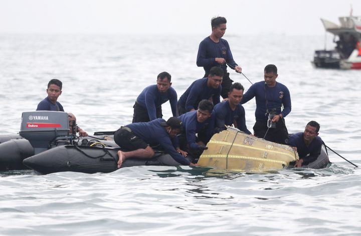 Indonesian Navy divers pull out a part of an airplane out of the water during a search operation for the Sriwijaya Air passen