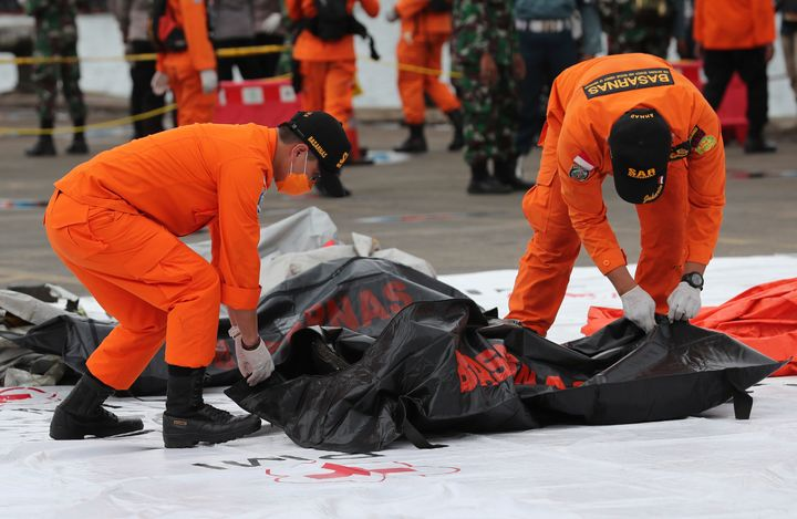 Rescuers carry a body bag containing human remains recovered from the waters where Sriwijaya Air passenger jet crashed.