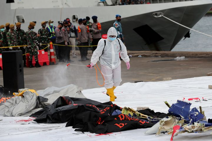 A workers sprays disinfectant on body bags containing the remains of passengers of Sriwijaya Air Flight 182 that crashed in t