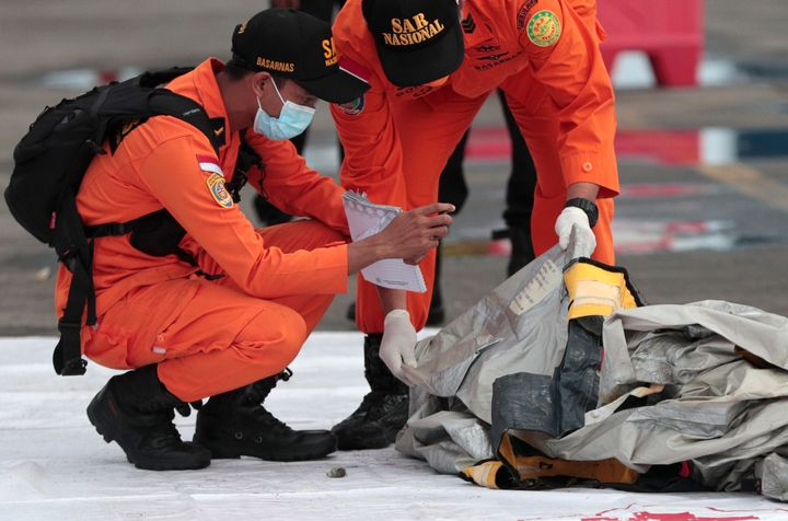Rescuers inspect debris found in the waters around the location where a Sriwijaya Air passenger jet has lost contact with air