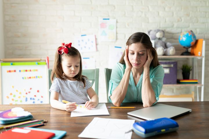 A stock photo of a mother with child during attempting to help with online school.